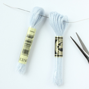 Cut the skein of thread in half and thread a 20cm (8in) length of wire through the loops.