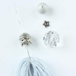 Thread on the bead cap, crystal, heishi star spacer and the pearl.