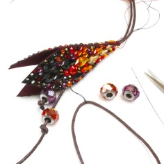 Add a second length of cord with a loop of thread. Use a long needle to stitch inside and secure at the top wrapping. Add be charmed beads and knot at different heights.